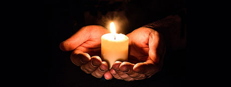 Image of hand holding candle by Myriam Zilles